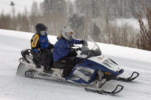 Riding a snowmobile with a passenger