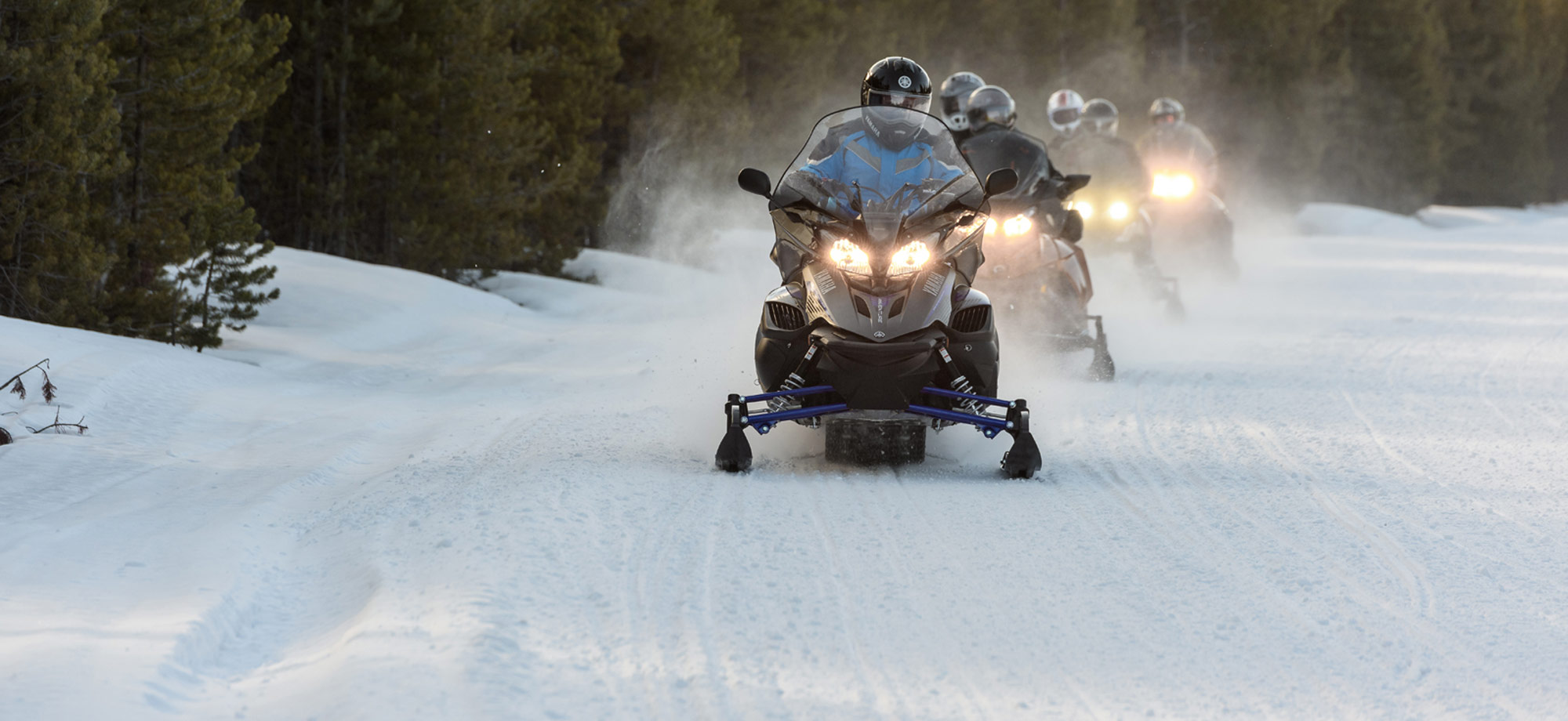 Snowmobilers riding in formation along trail