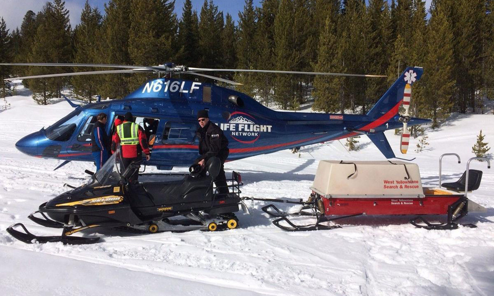 Helicopter rescuing snowmobiler