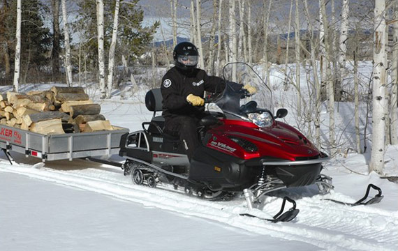 A snowmobiler towing a utlity sled